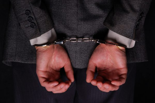 Close-up. Arrested businessman handcuffed hands at the back